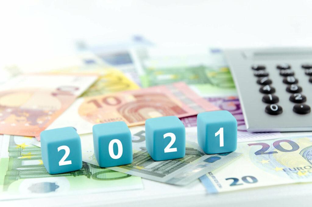 Geldscheine, Taschenrechner und Würfel mit Zahlen 2021